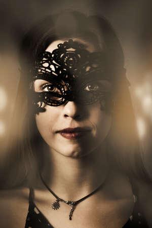 antifaz: Dram�tico retrato oscuro en la cara de una mujer joven y bella en el baile de la noche de lujo en misteriosa m�scara de la mascarada. Chica fiestera con clase Foto de archivo