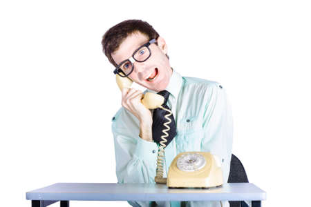 annoying: Young funny telemarketing businessman sitting at table with retro telephone, annoying call center clerk concept, white background