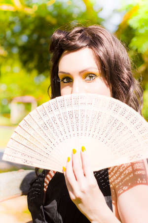 minx: Fashionable Female Summer Model Holds Up A Ornamental Fan While Posing In A Lush Outdoor Meadow In A Summer Fashion Scene Stock Photo