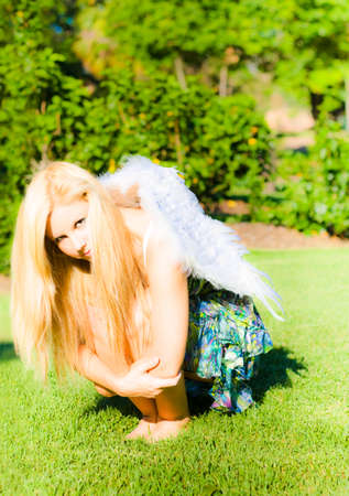 cowering: Woman with long blonde hair squatting arms around her knees, with feather wings on her back in a broken wings concept
