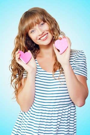 donna innamorata: Ritratto di una giovane donna felice con il simbolo di amore cuore su sfondo blu studio