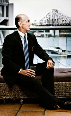 verandah: Senior Executive Sitting On A Waterfront House Verandah Looking Out To The Distance With A Positive Future Outlook, Photograph Taken Brisbane City, Australia Stock Photo