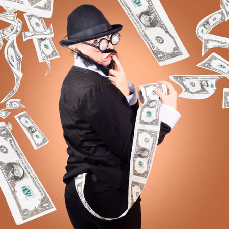 sleazy: Wealthy businessman looking for way to stash a large sum of American dollars notes printed on a toilet roll in a depiction of dirty money Stock Photo
