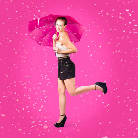 dashing: Dashing retro pinup girl popping up one leg with umbrealla when doing a rain dance in fifties fashion. Pink background