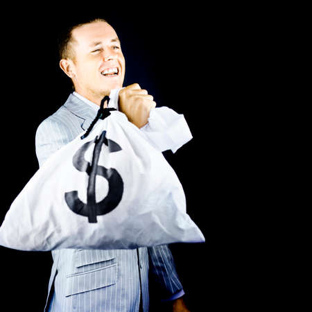 boastful: Young stylish businessman with a money bag full of dollars slung over his shoulder laughing in glee in a conceptual image of the metaphor Laughing all the way to the bank
