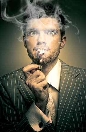 underpaid: A Haze Of Stress And Smoke Is In The Air As A Underpaid And Overworked Business Man Lights Up Three Cigarettes In A Unhealthy Habit of Sadness And Loneliness