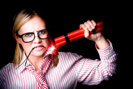 vindictive: Female Businessperson holding a stick of explosives threatening strike action in a work union concept on black Stock Photo