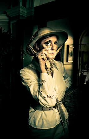 médula: Explorador de la vendimia Intrepid en ropa de color caqui safari y casco de médula mirando a través de un vaso pequeño ojo monóculo en las sombras de la noche mientras busca aventura y descubrimiento