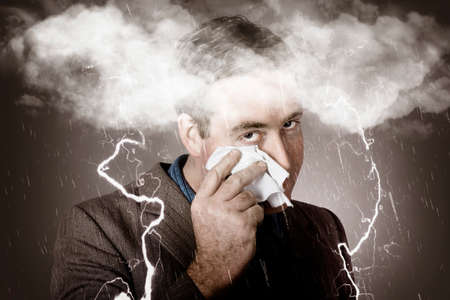 bad business: Creative portrait of a sad and unhappy businessman crying in a windy head storm of rain and lightning. Bad business outlook
