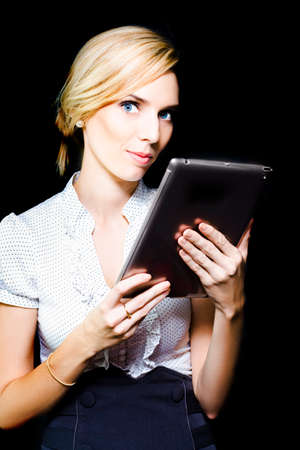 assessing: Beautiful stylish professional blonde woman holding a touch screen tablet with the screen facing herself and looking up with an attentive assessing expression on a black studio background Stock Photo