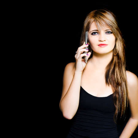 sales rep: Isolated studio portrait of a attractive young business woman using a mobile phone during a office teleconference call, image with copyspace and black background Stock Photo