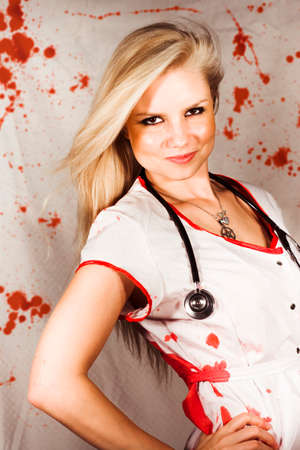 Beautiful sadistic nurse in a bloody uniform giving an evil smirk of satisfaction standing in front of blood spattered cutains Stock Photo