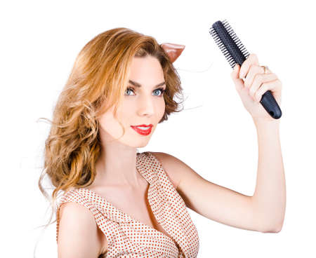 strawberry blonde: Retro pin up woman combing wavy strawberry blonde hairstyle. Hair care Stock Photo