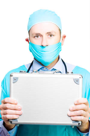 sturdy: Doctor in mask and gown holding a metal first aid kit as he extols the virtues of having a sturdy allweather medical container in case of emergencies Stock Photo