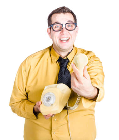 antique telephone: An excited nerdy man in yellow shirt holding a antique telephone reciever when giving great news