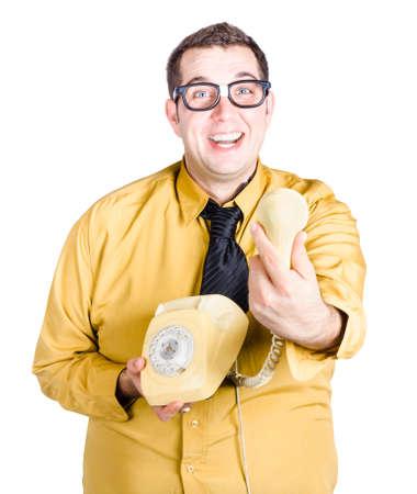 telefono antico: Un uomo nerdy eccitato in camicia gialla in possesso di un ricevitore telefonico antico quando d� una grande notizia Archivio Fotografico