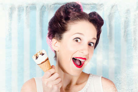 freezer: Retro ice cream poster girl holding cone inside cold freezer with vintage hairstyle and make-up. Summer chill out