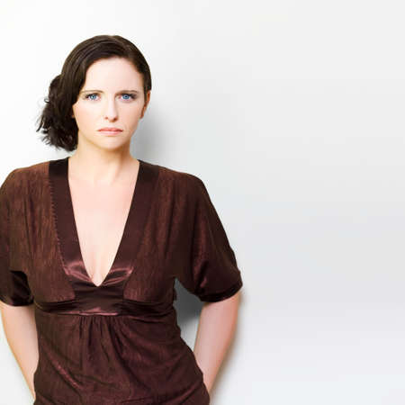 inhibited: Beautiful stylish brunette woman with an unsmiling unimpressed expression staring directly at the camera isolated on white in an Unhappy woman concept Stock Photo