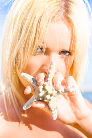 obscuring: Attractive Female Holding Starfish In Front Of Mouth With Mysterious Expression As If To Represent That She Will Not Share Her Summer Secrets