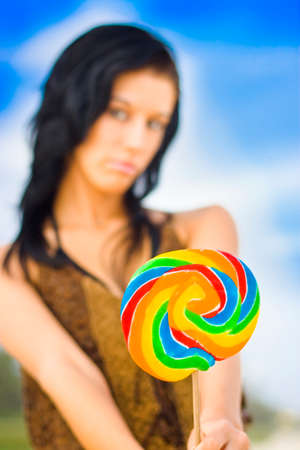 offers: Cute Young Woman With Black Hair Holding A Rainbow And Delicious Lollipop As An Offering With Sweet And Innocent Expression On Her Face
