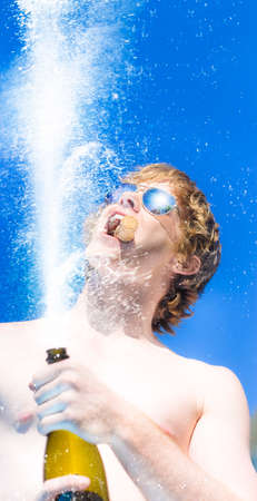 bubbly: Low angle image of a mans hands holding a champagne bottle with a spray of bubbly and his face above against a blue sky