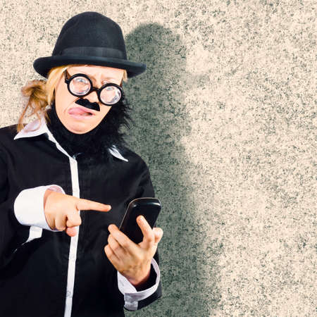 troubleshoot: Funny grunge portrait of a geek businessman having difficulty with modern technology when text messaging on mobile smart phone. Technology troubleshoot concept Stock Photo