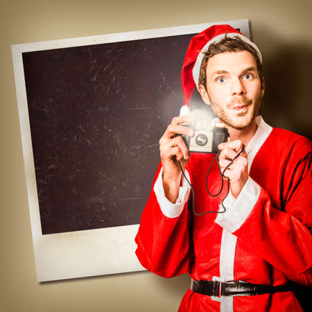 photo pictures: Little elf holding camera in front of copy space photo frame while taking christmas pictures with santa