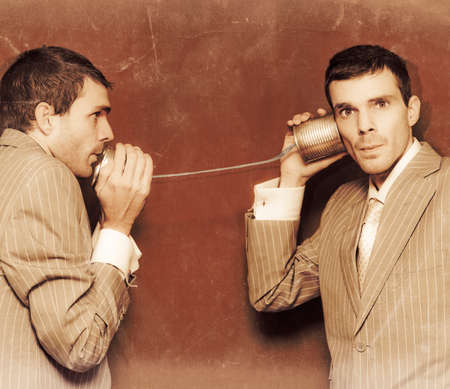 dos personas conversando: Fotografía de la vendimia de dos personas el intercambio de información en la línea de una lata de teléfono en una comunicación retro conceptual Foto de archivo