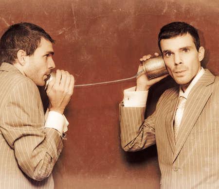 communicatie: Vintage foto van twee mensen uit het bedrijfsleven uitwisselen van informatie langs de lijn van een telefoon van het tinblik in een retro Communicatie Conceptueel