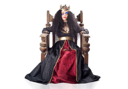 enthroned: Young woman dressed as a queen with matching robes and gold crown seated on wooden throne isolated on white background