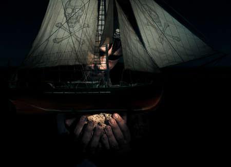 coger: Supernatural oscura y misteriosa aventura concepto con una gigante pirata Sostiene Una Capturado barco pirata que simboliza una búsqueda de la travesía y Exploración