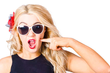 astounded: Crazy isolated portrait of a shocked blonde woman wearing sunglasses with pin-up makeup pressing cheek in a depiction of cosmetic application