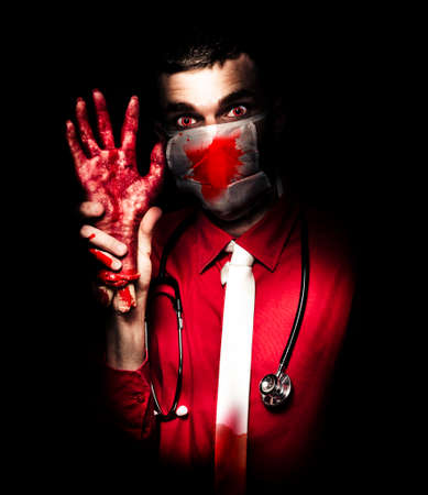 psychopath: Creepy Psychopathic Pathologist Standing In The Darkness Holding A Sawn Off Hand In A Depiction Of A Autopsy Dissection