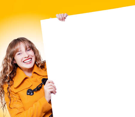 saleslady: Happy laughing young blonde woman in a warm bright orange winter coat holding up a blank white board from the side for your text or advertisment Stock Photo
