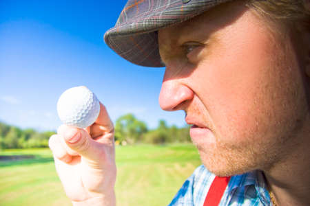 squabble: Upset Golfer Has A Mid Game Crisis While Arguing With The Golf Ball He Is Holding In A Funny And Humorous Sport Concept Stock Photo