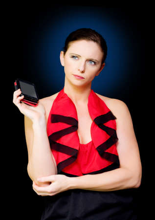 voicemail: Corporate woman holding mobile phone while thinking in a image titled Think Smart And Work Mobile on dark studio background Stock Photo