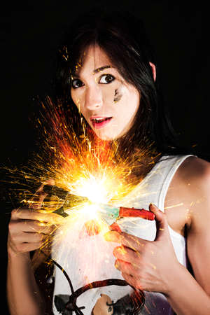 electrocute: Woman bringing together postive and negative cable clamps on a jump start battery kit resulting in a fiery explosion Stock Photo
