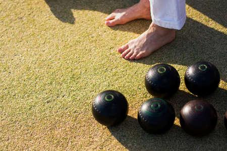 pies descalzos: Los pies descalzos y las bolas de bolos en un c�sped verde cuencos