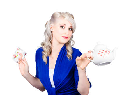 stand teapot: Pretty blonde girl in bright blue outfit is holding a kettle and a cup Stock Photo