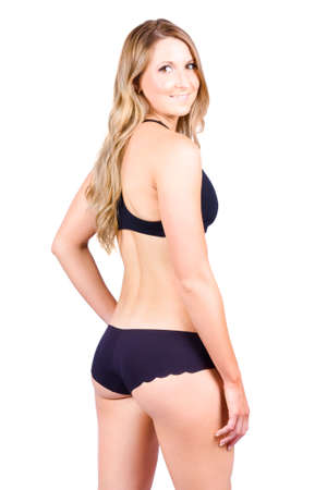 woman looking: Rear view of young blond woman in swimwear looking over shoulder, white background.