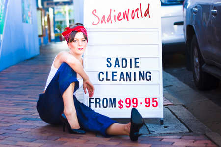 clean street: Sadie The Cleaning Lady Marketing Her House Clean And Tidy Service While Sitting Next To A Sadieworld Advertising Sign On The Street