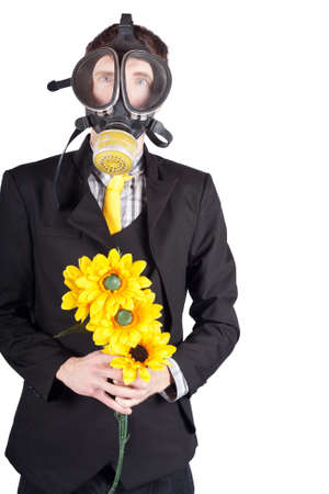 enviro: Environmental man in a gas mask holding a bouquet of yellow sun flowers. Carbon pollution concept. Stock Photo