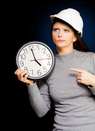despaired: Female Construction Builder Pointing At Clock Signaling Impending Deadline Of A Unfinished Project