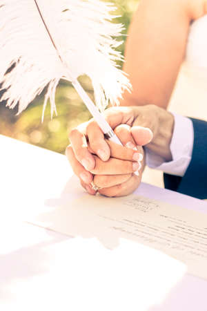 vow: A Tender Pledge Of Commitment Sees A Bride And Groom Hold Hands And A Writing Quill To Sign The Wedding Register Booklet In A Vow Affirmation