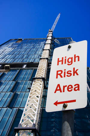 assemblage: Crane Strapped To The Side Of A Structure Under Construction With A High Risk Area Safety Sign
