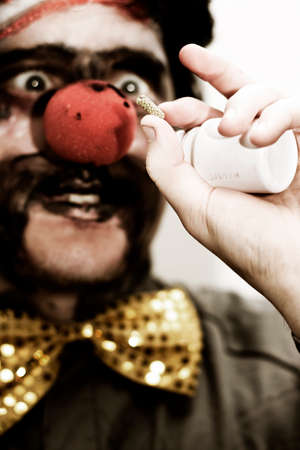 prescribed: Darkened Image Of A Clown Holding Up A Prescribed Medication Tablet To Help Bring His Humor Back