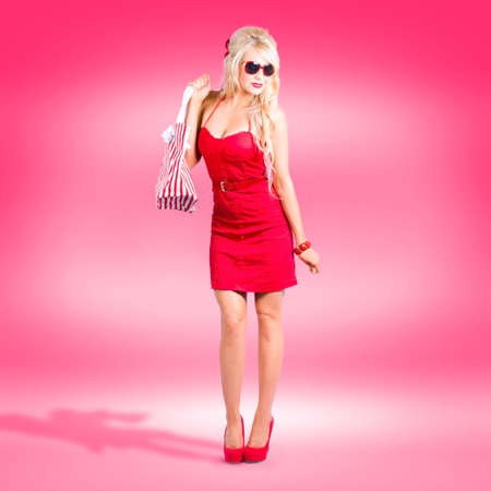 spendthrift: Female retail shopper in stylish red dress with matching high heel shoes and carry bag. Ready to shop.