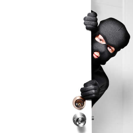 thief: Home burglary concept with a burglar sneaking in a open house door during a break and enter past security locks and alarms, white background with copyspace
