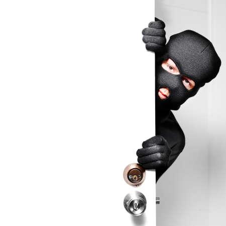 ladron: Inicio concepto de robo con un ladrón a escondidas en una puerta de la casa abierta durante un descanso y entrar cerraduras de seguridad y alarmas, pasados ??fondo blanco con copyspace