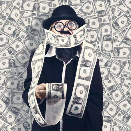 moneyed: Billionaire male business person making money on the roll when covered in one dollar USD bills. Financial success concept
